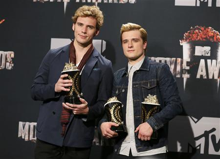 Sam Claffin y Josh Hutcherson sostienen sus premios